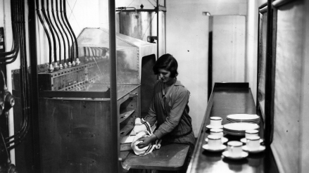 Maid prepares a meal in the kitchen of the R100.