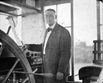 Capt. Bruce Barnes stands at the wheel in the pilothouse