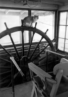 A cat sits atop the wheel in the pilothouse of an unknown steamer
