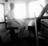 A man sits at the wheel in the pilothouse of the Str. Delta Queen