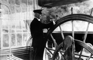 Pilot Lawrence H. Sanders at the wheel of the U. S. Mississippi River Commission Inspection Boat Mississippi, 1907