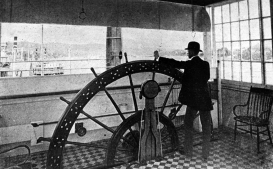 A pilot stands at the wheel in the pilothouse of an unknown riverboat