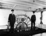 Captain Ben Pattison and Pilot Harry W. Doss stand beside the wheel in the pilothouse of the Str. Island Queen
