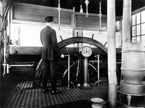 Pilot Harry English at the wheel in the pilothouse of the Str. Queen City, 1918