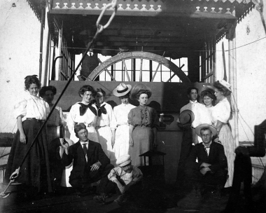 A group of passengers pose near the pilothouse on the hurricane deck of the Str. Eclipse