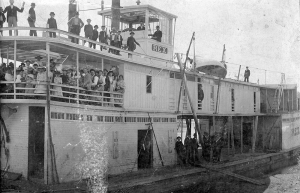 Men, women and children standing on the decks of the Str. Rex while she is at shore