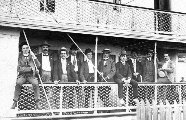 Men crowd the rails of the Str. St. Lucie