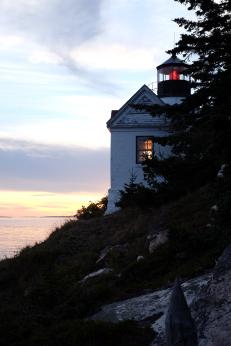 Sunset lights the window of the Bass Harbor Head Lighthouse (Photo by Kari-Lise)