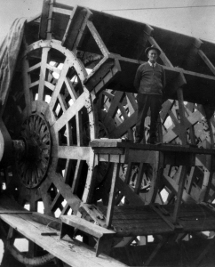 A man is standing on a bucket of a paddlewheel