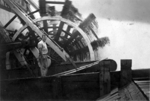 Deckhand standing next to the sternwheel in motion