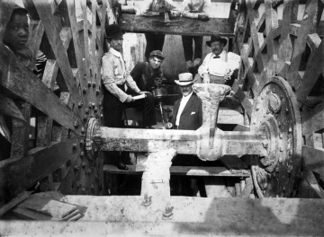 Deckhands standing in and around the paddlewheel of an unknown boat for maintenance in the late 19th century/early 20th century