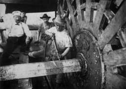 Group of deckhands standing next to a paddlewheel of an unknown boat for maintenance in the late 19th century/early 20th century