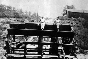 Two men sit atop an enormous paddlewheel in dry dock