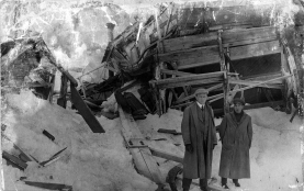 Two men stand near the paddlewheel of the wreckage of an unidentified steamboat on snow covered ground at St. Louis