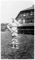 A mummy-like figure standing in front of a barn, 1919